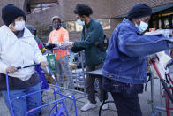 Volunteers and employees give out food to people waiting in line at the Doles Center in Mt. Vernon, N.Y., Monday, Nov. 16, 2020. While this particular aid was donated by Goya Foods, over the course of 2020 the city's recreation department is on track to give away almost three times more food, over one million pounds, than the usual amount they would help within a normal year. (AP Photo/Seth Wenig)