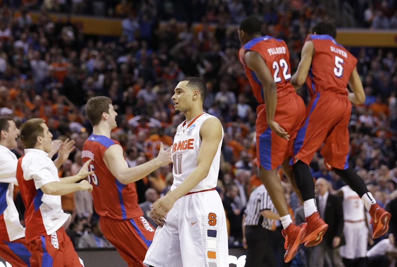 Syracuse's Tyler Ennis (11) reacts as Dayton's Kendall Pollard (22) and Devin Oliver (5) celebrate with teammates during the second half of a third-round game in the NCAA men's college basketball tournament in Buffalo, N.Y., Saturday, March 22, 2014. Dayton won 55-53. (AP Photo/Frank Franklin II)