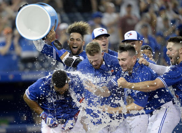 Toronto Blue Jays center fielder Teoscar Hernandez (37) is celebrated with a sports drink shower by teammates after his walk-off home run in 12th inning of a baseball game against the Tampa Bay Rays, Saturday, July 27, 2019 in Toronto. (Nathan Denette/Canadian Press via AP)
