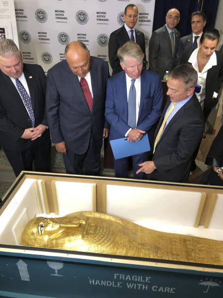 U.S. Homeland Security Investigations special-agent-in-charge Peter Fitzhugh, left, Egyptian Minister of Foreign Affairs Hassan Shoukry center left, Manhattan District Attorney Cyrus Vance Jr., center right and Assistant District Attorney Matthew Bogdanos view the Coffin of Nedjemankh at a repatriation ceremony in New York, Wednesday, Sept. 25, 2019. The coffin, featured at New York's Metropolitan Museum of Art until it was determined to be a looted antiquity, is on its way back to Egypt. (AP Photo/Michael R. Sisak)