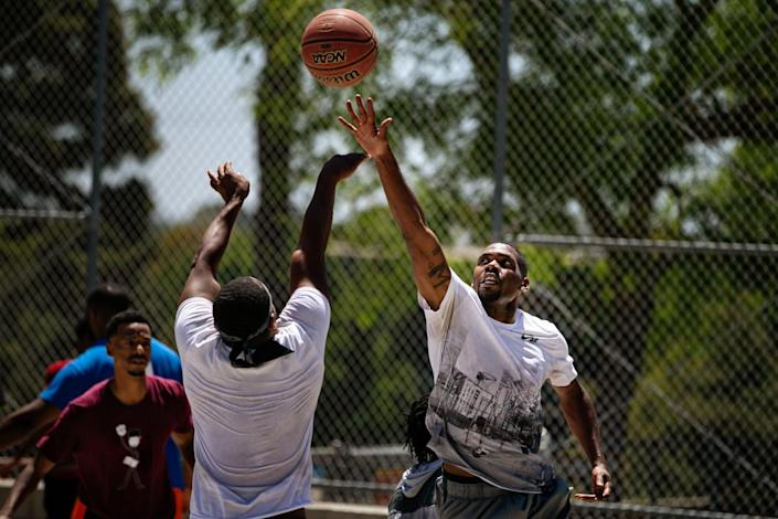 Two players reach for a basketball during a game