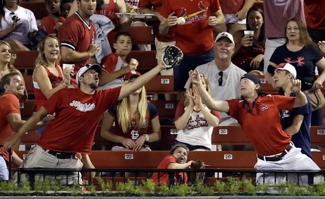 Fans try to catch a ball hit for a solo home run by St. Louis Cardinals' Allen Craig during the sixth inning of a baseball game against the San Francisco Giants, Thursday, May 29, 2014, in St. Louis. (AP Photo/Jeff Roberson)