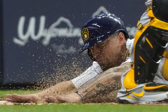 Milwaukee Brewers' Jace Peterson slides safely past Pittsburgh Pirates catcher Michael Perez during the second inning of a baseball game Friday, June 11, 2021, in Milwaukee. Peterson scored from third on a bunt by Brandon Woodruff. (AP Photo/Morry Gash)