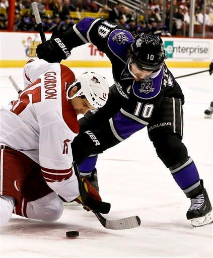 Los Angeles Kings' Mike Richards (10) battles Phoenix Coyotes' Boyd Gordon (15) for the puck after a face-off in the first period during an NHL hockey game Tuesday, March 12, 2013, in Glendale, Ariz. (AP Photo/Ross D. Franklin)