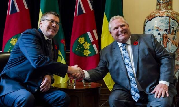Ontario Premier Doug Ford and Saskatchewan Premier Scott Moe pose in 2019. Ford has asked Moe to send health-care workers to his province, sources say. (Christopher Katsarov/The Canadian Press - image credit)