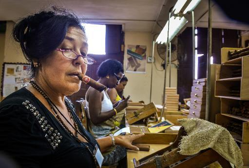 <p>Workers make cigars at the H.Upmann cigar factory in Havana, on February 27, 2014</p>