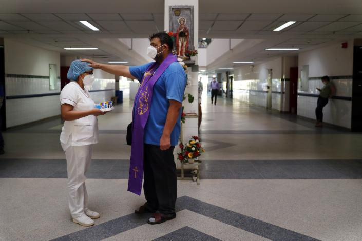 Catholic priest Juan Carlos Ayala blesses a nurse at the Clinicas Hospital in San Lorenzo, Paraguay, Monday, May 17, 2021. Ayala is a Franciscan Order priest that walks along the hospital's corridors blessing workers and the relatives of COVID-19 patients. (AP Photo/Jorge Saenz)