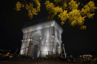 """Workers wrap the Arc de Triomphe monument, Wednesday, Sept. 15, 2021 in Paris. The """"L'Arc de Triomphe, Wrapped"""" project by late artist Christo and Jeanne-Claude will be on view from, Sept. 18 to Oct. 3. The famed Paris monument will be wrapped in 25,000 square meters of fabric in silvery blue, and with 3,000 meters of red rope. (AP Photo/Francois Mori)"""