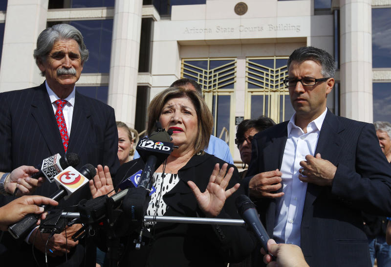 Mary Rose Wilcox, center, a Maricopa County Board of Supervisors member who had a criminal case brought against her by then-Maricopa County Attorney Andrew Thomas, speaks in front of the Arizona State Courts building after an ethics panel moved to disbar Thomas Tuesday, April 10, 2012, in Phoenix. , Her husband Earl Wilcox, left, and Randy Parraz, president of Citizens For A Better Arizona, listen.  An Arizona ethics panel ruled to disbar Maricopa County's former top prosecutor for failed corruption investigations he and America's self-proclaimed toughest sheriff conducted targeting officials with whom they were having political and legal disputes. (AP Photo/Ross D. Franklin)