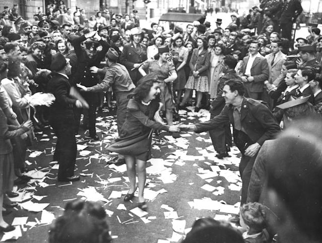 British girls, of the Picture Division of the London Office of War Information, dance in the street with American soldiers during the V-E Day celebrations in London, May 8, 1945. (Photo by Photo12/UIG/Getty Images)
