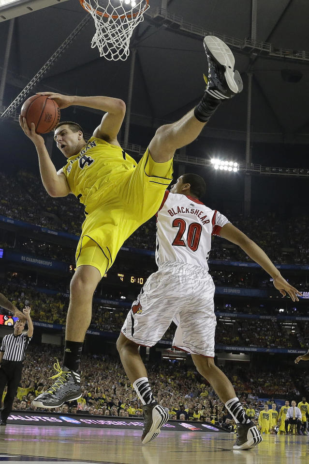"""FILE - In this April 8, 2013 file photo, Michigan forward Mitch McGary (4) comes down with the rebound as Louisville guard/forward Wayne Blackshear (20) looks on during the first half of the NCAA Final Four tournament college basketball championship game in Atlanta. McGary is entering the NBA draft, saying he had little choice after testing positive for marijuana during the NCAA tournament. """"I am ready to move on to the next stage in my life and enter the NBA draft,"""" the 6-foot-10 McGary said in a statement released by the school Friday, April 25, 2014. (AP Photo/David J. Phillip, File)"""
