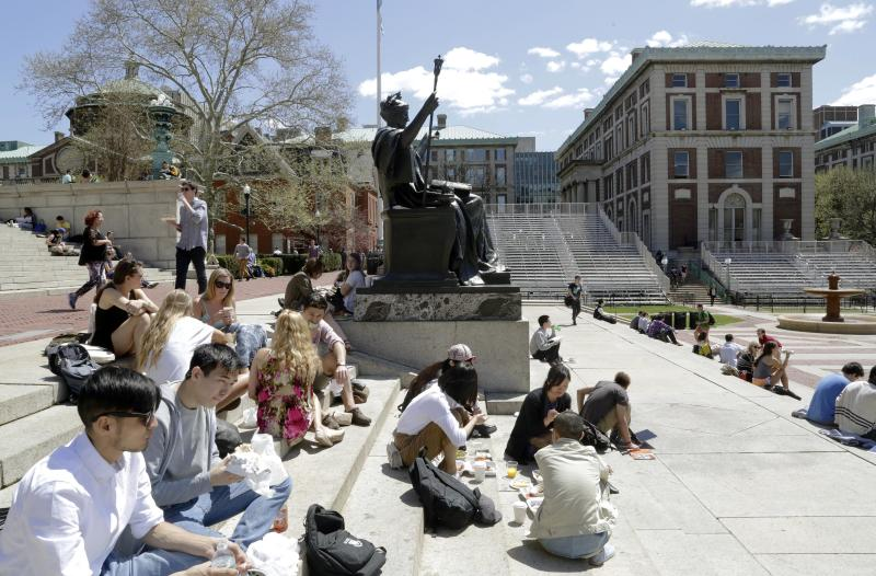 FILE - In this April 29, 2015 file photo, students sit on the steps of Columbia University's Low Memorial Library next to Daniel Chester French's sculpture, Alma Mater, on the school's campus in New York. A new coalition of students and alumni from 11 top U.S. colleges, including Columbia, are asking their schools in 2018 to rethink legacy admissions policies. (AP Photo/Mark Lennihan, File)