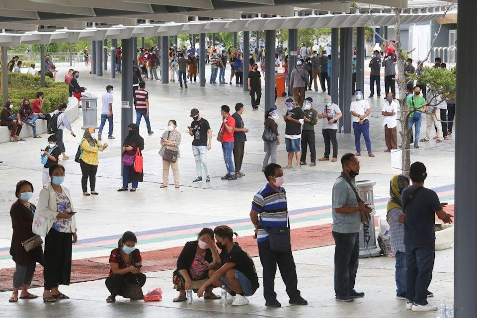 Foreign workers queue as they wait to get their Covid-19 jab at the Bukit Jalil Stadium vaccination centre August 10, 2021. ― Picture by Choo Choy May