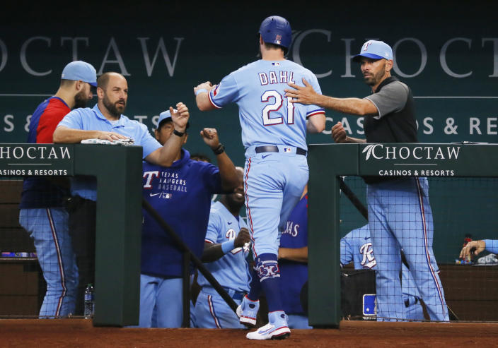 Texas Rangers' David Dahl, center, is greeted at the dugout steps by manger Chris Woodward, right, after scoring against the Oakland Athletics during the fifth inning of a baseball game in Arlington, Texas, Sunday, July 11, 2021. (AP Photo/Ray Carlin)