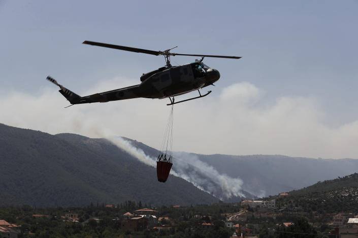A Lebanese army helicopter takes off from a water storage point after it refilled a tank to extinguish a forest fire, at Qobayat village, in the northern Akkar province, Lebanon, Thursday, July 29, 2021. Lebanese firefighters are struggling for the second day to contain wildfires in the country's north that have spread across the border into Syria, civil defense officials in both countries said Thursday. (AP Photo/Hussein Malla)