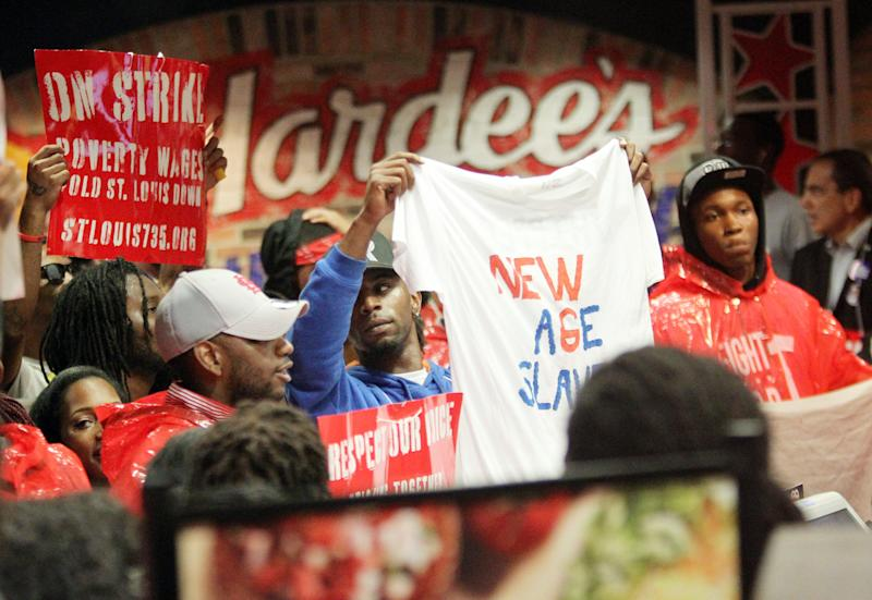 FILE - In this Tuesday, July 30, 2013 file photo, demonstrators fill the Hardees on Chestnut in Downtown St. Louis. On Thursday, Aug. 29, 2013, organizers say thousands of workers are set to stage walkouts in at least 50 cities around the country, part of a push to intensify the spotlight on the wages paid by chains such as McDonald's, Taco Bell and Wendy's. (AP Photo/Belleville News-Democrat, Derik Holtmann)