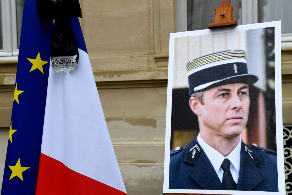 a portrait of French Lieutenant-Colonel Arnaud Beltrame is pictured during a minute of silence, on March 28, 2018 at the Interior Ministry in Paris. France honours during a national ceremony on March 28 a heroic policeman who died offering himself as a hostage in a jihadist attack. Beltrame, 44, was the fourth and final victim in the shooting spree on March 23 in the southwestern towns of Carcassonne and nearby Trebes. / AFP PHOTO / BERTRAND GUAY (Photo credit should read BERTRAND GUAY/AFP/Getty Images)