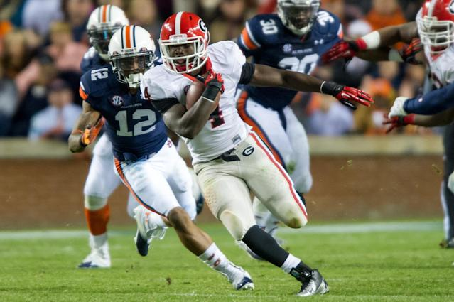 AUBURN, AL - NOVEMBER 10: Tailback Keith Marshall #4 of the Georgia Bulldogs runs past defensive back Demetruce McNeal #12 of the Auburn Tigers for a first down late in the first half on November 10, 2012 at Jordan-Hare Stadium in Auburn, Alabama. Georgia leads Auburn 28-0 at halftime. (Photo by Michael Chang/Getty Images)