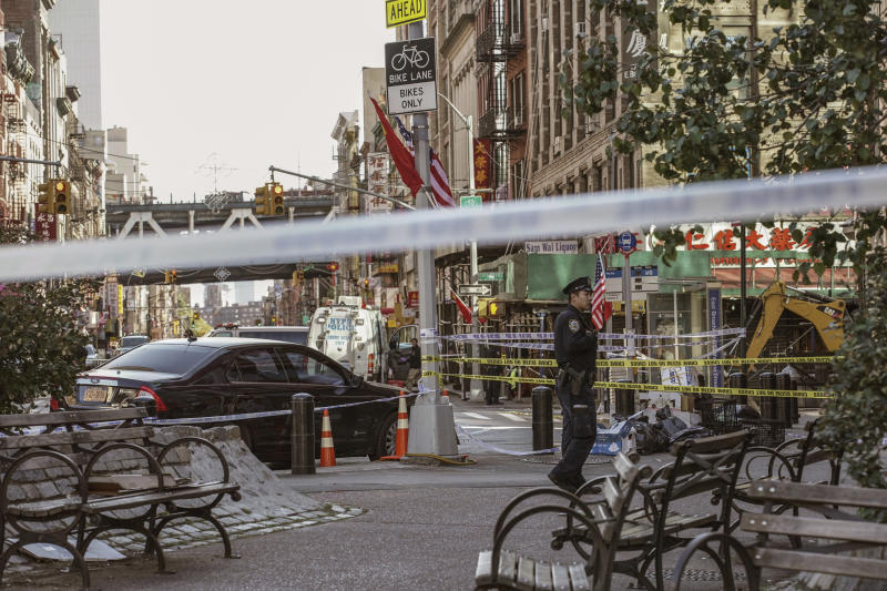 New York Police Department officers investigate the scene of an attack in Manhattan's Chinatown neighborhood, Saturday, Oct. 5, 2019 in New York.  Four men who are believed to be homeless were brutally attacked and killed early Saturday in a street rampage. NYPD Detective Annette Shelton said that a fifth man remained in critical condition after also being struck with a long metal object that authorities recovered. (AP Photo/Jeenah Moon)
