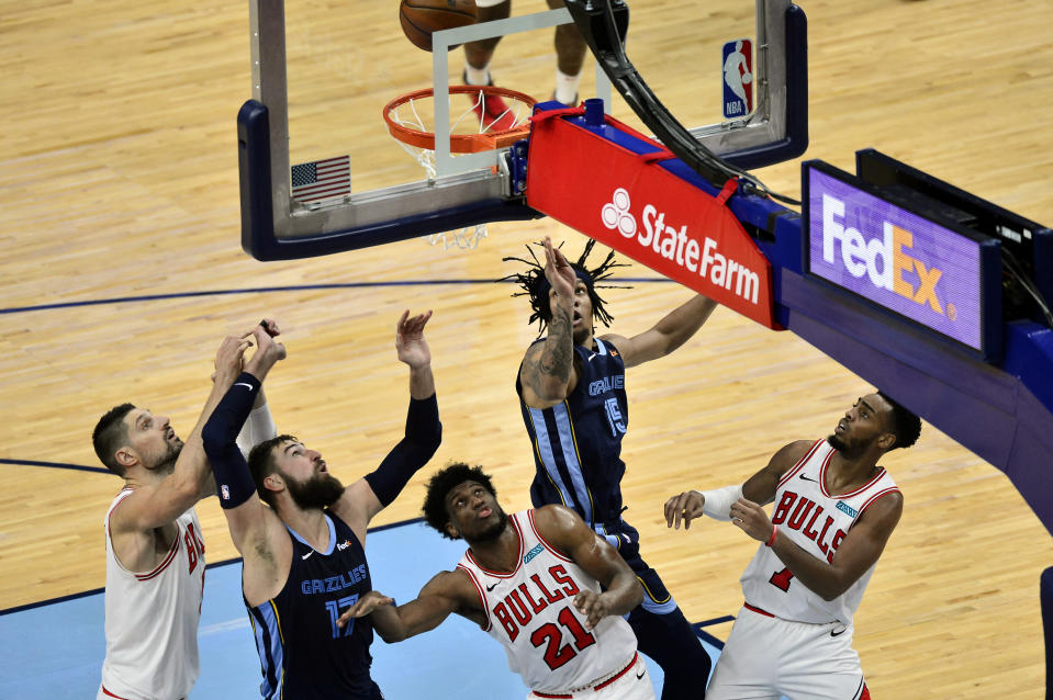 Memphis Grizzlies forward Brandon Clarke (15) tips in a rebound to score as Chicago Bulls center Nikola Vucevic (9), Grizzlies center Jonas Valanciunas (17), and Bulls forwards Thaddeus Young (21), and Troy Brown Jr. (7) move for position under the goal in the second half of an NBA basketball game Monday, April 12, 2021, in Memphis, Tenn. (AP Photo/Brandon Dill)