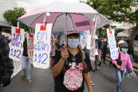"""A pro-democracy supporter wears a face mask with the umbrella with sign saying """"No to Article 112"""", a legal provision in Thailand's Criminal Code concerning any defamation of the monarchy, as she participates in a rally in Bangkok, Thailand, Thursday, June 24, 2021. Anti-government protests expected to resume in Bangkok after a long break due partly to a surge in COVID-19 cases. Gatherings are planned for several locations across the capital, despite health officials mulling a week-long lockdown in Bangkok to control a rampant virus surge. (AP Photo/Sakchai Lalit)"""