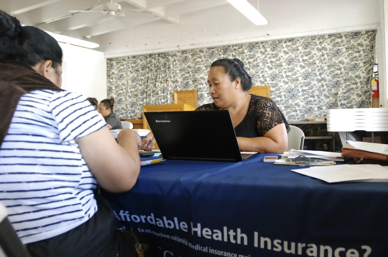 FILE - In this Jan. 30, 2017 file photo, Cinder Sonis, right, an advocate with Legal Aid Society of Hawaii, helps a customer enroll in an Affordable Care Act health insurance plan in Honolulu. Allowing insurers to market health care policies across state lines is one of President Donald Trump's main ideas for bringing down costs. While supporters of the idea cast it as a way to make insurance policies more competitive, critics say it's unlikely to result in more affordable plans and could undermine stronger consumer protections in states such as California and Hawaii. (AP Photo/Cathy Bussewitz, File)