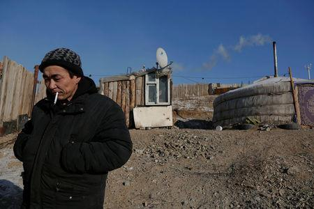 Setevdorj Myagmartsogt smokes a cigarette outside his tent-like ger home, which is heated by coal burning stove, in Ulaanbaatar, Mongolia January 29, 2017. Setevdorj Myagmartsogt lives with his wife, four children and two relatives in his ger near a coal depot not far from the centre of the Mongolian capital. REUTERS/B. Rentsendorj