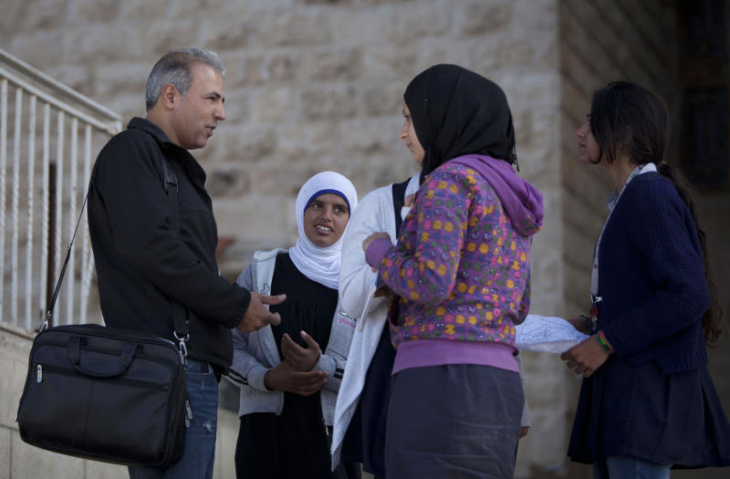 In this Thursday, April 3, 2014 photo, Palestinian Esmat Mansour, a former prisoner who was released after 20 years in Israeli jail, talks to his Hebrew students at a school in the village of Taybeh, near the West Bank city of Ramallah. Mansour was 16 when, in October 1993, he helped three older teens stab to death an Israeli man. Mansour said the time in Israeli prison changed him. (AP Photo/Majdi Mohammed)