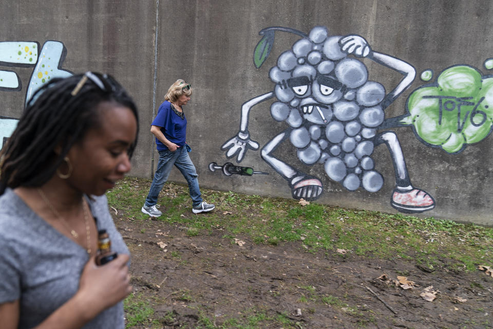 Larrecsa Cox, foreground, and Sue Howland with the Quick Response Team, walk past addiction-themed graffiti near a tent encampment along the river looking to check-in with a client who recently overdosed in Huntington, W.Va., Wednesday, March 17, 2021. The Centers for Disease Control and Prevention estimates that more than 88,000 people died of drug overdoses in the 12 months ending in August 2020, the latest figures available. That represents the highest number of overdose deaths ever recorded. (AP Photo/David Goldman)