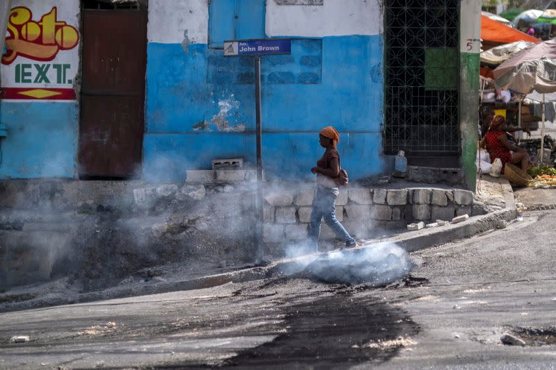 A woman walks past a smoking tire set on fire by protesters upset with growing violence