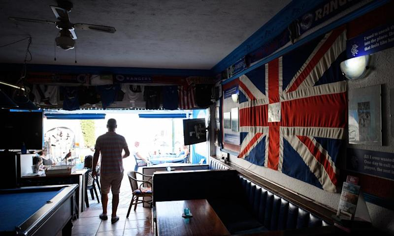 A man walks past a large Union flag in the Bar None in Benalmadena, Spain.