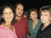 This 2004 photo provided by Peter Milian shows his cousin, Marcus Guara, center left, during the 70th birthday of his mother, Elsita Guara, center right, with his aunt, Lourdes Galan-Milian, right, and his sister, Annette Guara-Hurst, left. The remains of Marcus Guara, 52, were the first to be pulled from the rubble of the Champlain Towers South in Surfside, Fla., on Saturday, June 26, 2021. His daughters, 10-year-old Lucia, and 4-year-old Emma, and their mother, Anaely, were recovered Wednesday, June 30, 2021. (Peter Milian via AP)