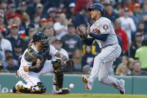 Houston Astros' Michael Brantley, right, scores on a single by Yuli Gurriel as Boston Red Sox's Christian Vazquez, left, drops the ball during the first inning of a baseball game in Boston, Saturday, May 18, 2019. (AP Photo/Michael Dwyer)