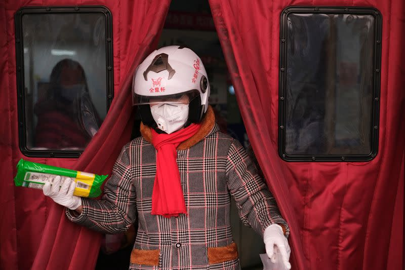 A woman wearing a face mask walks out of a supermarket, as the country is hit by an outbreak of the new coronavirus, in Beijing