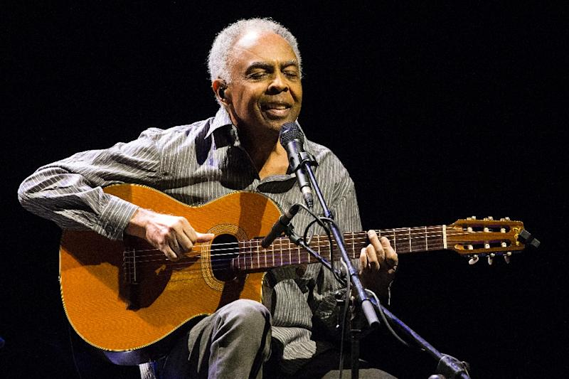 Picture of Gilberto Passos Gil Moreira singing at a microphone and playing guitar