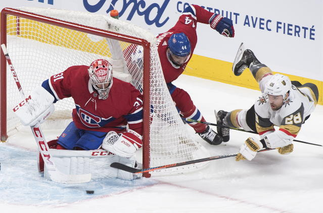 Vegas Golden Knights' William Carrier (28) lunges for the puck as he moves in against Montreal Canadiens goaltender Carey Price as Canadiens' Nate Thompson (44) defends during first-period NHL hockey game action in Montreal, Saturday, Jan. 18, 2020. (Graham Hughes/The Canadian Press via AP)