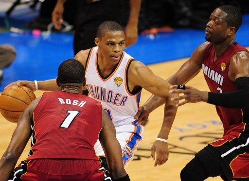 Oklahoma City Thunder's Russell Westbrook (C) drives the ball past Miami Heat's Chris Bosh (L) and Dwyane Wade during game one of the NBA Finals on June 12. Oklahoma City delivered the first blow of the best-of-seven championship series with a 105-94 win