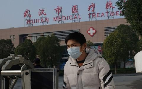 A man leaves the Wuhan Medical Treatment Centre, where a man who died from a respiratory illness was confined - Credit:  NOEL CELIS/AFP/Getty