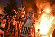 A Lebanese protester flashes the victory sign amid clashes with security forces in the centre of Beirut on Tuesday night