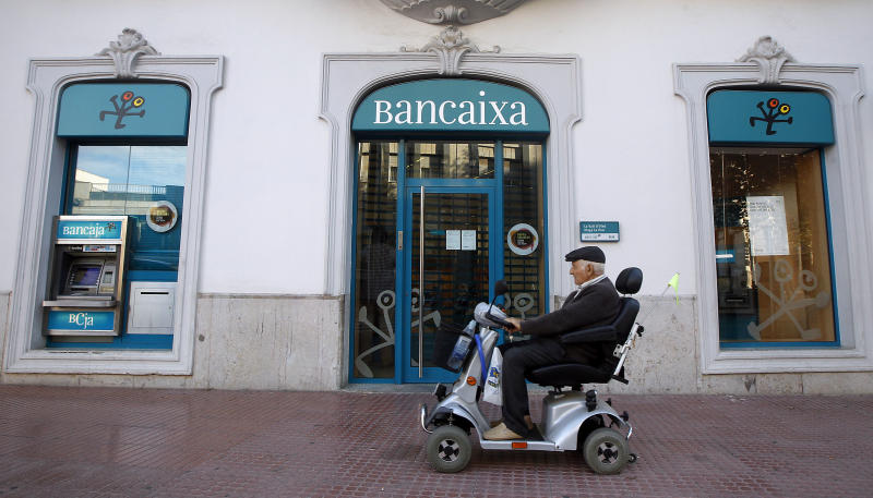 In this photo taken Oct 23, 2012, a disabled man passes a Bancaixa regional savings bank that is now part of Spanish banking giant Bankia in La Vall D'Uixo, near Valencia, Spain. Thousands of townspeople and nearly a million across Spain followed bank manager's advice and invested their life savings in the bank's stocks. Lured by the family-like ties nurtured between bankers and customers, they poured their life's savings into higher-yielding financial instruments recommended by the people managing their money. When boom turned to catastrophic bust, they found the stock they had acquired had become all but worthless. (AP Photo/Alberto Saiz)