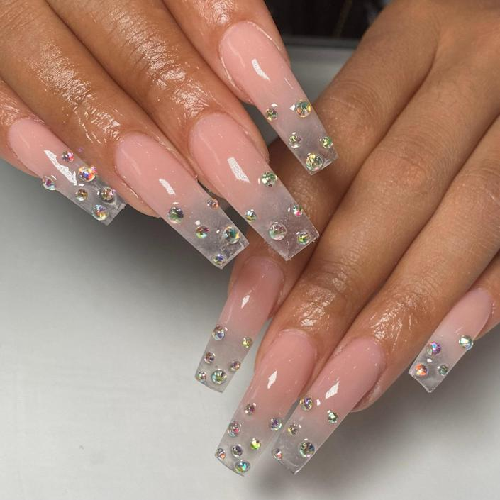 """Emilius added texture to this clear manicure for a <a href=""""https://www.allure.com/story/wet-nail-art-trend?mbid=synd_yahoo_rss"""" rel=""""nofollow noopener"""" target=""""_blank"""" data-ylk=""""slk:&quot;wet&quot; effect"""" class=""""link rapid-noclick-resp"""">""""wet"""" effect</a>. She created a clear ombré so the nail looks like it's fading from a light pink color to completely transparent. From the tips to about halfway down the nails, the iridescent droplets twinkle."""
