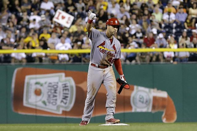 St. Louis Cardinals' Tony Cruz signals the dugout after driving in two runs with a double off Pittsburgh Pirates starting pitcher Jeanmar Gomez during the seventh inning of a baseball game in Pittsburgh on Thursday, Aug. 1, 2013. The Cardinals won 13-0. (AP Photo/Gene J. Puskar)