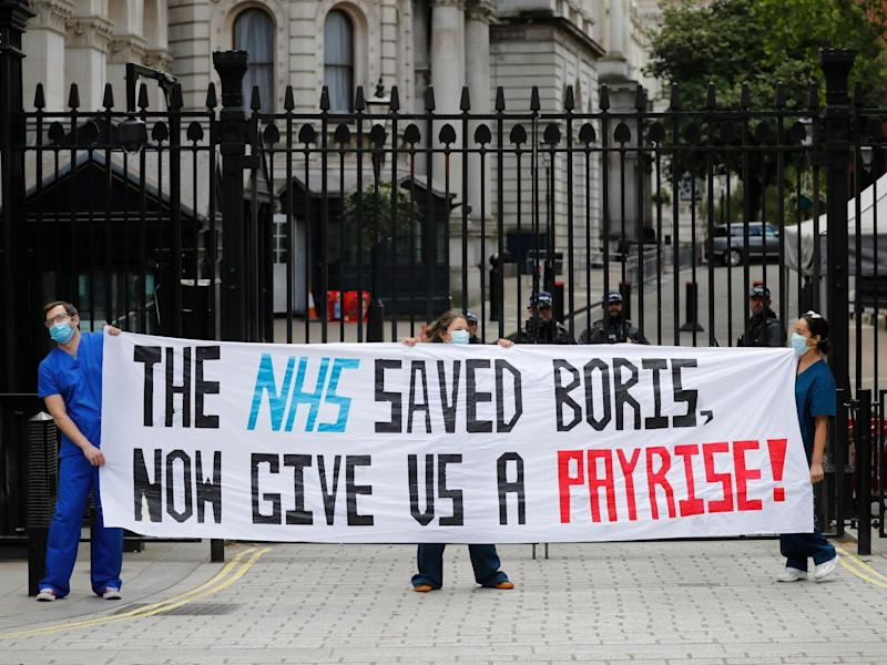 Nurses who work at central London hospitals protest with placards outside Downing Street: Getty