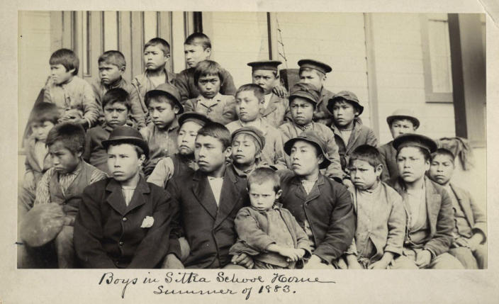This photo made available by the Presbyterian Historical Society, Philadelphia shows students at a Presbyterian boarding school in Sitka, Alaska in the summer of 1883. U.S. Catholic and Protestant denominations operated more than 150 boarding schools between the 19th and 20th centuries. Native American and Alaskan Native children were regularly severed from their tribal families, customs, language and religion and brought to the schools in a push to assimilate and Christianize them. (Presbyterian Historical Society, Philadelphia via AP)