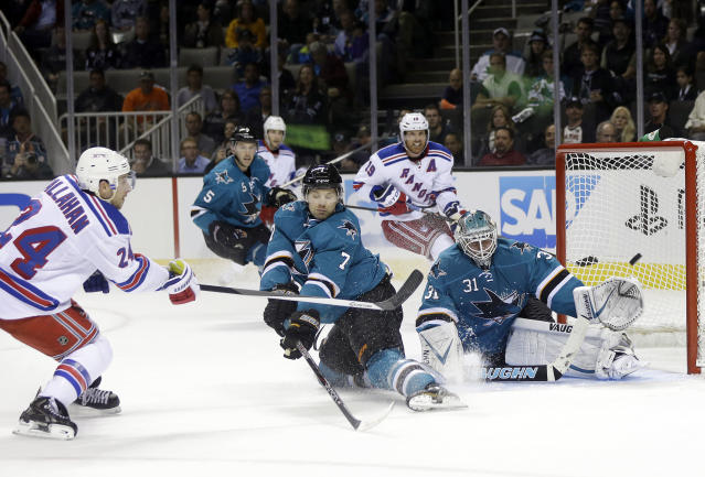 New York Rangers' Ryan Callahan (24) shoots next to San Jose Sharks' Brad Stuart (7) and Goalie Antti Niemi, right, of Finland during the second period of an NHL hockey game on Tuesday, Oct. 8, 2013, in San Jose, Calif. (AP Photo/Marcio Jose Sanchez)