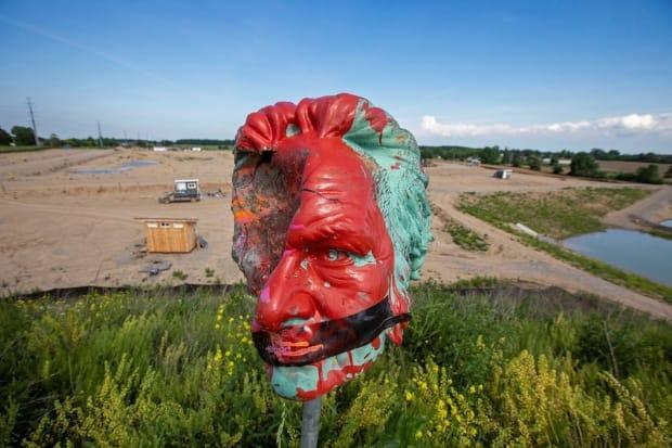 The head from a Ryerson University statue of Egerton Ryerson, one of the architects of Canada's residential school system, is seen after its removal, at 1492 Land Back Lane reclamation camp set up by Six Nations of the Grand River in Caledonia, Ont.  (Carlos Osorio/Reuters - image credit)