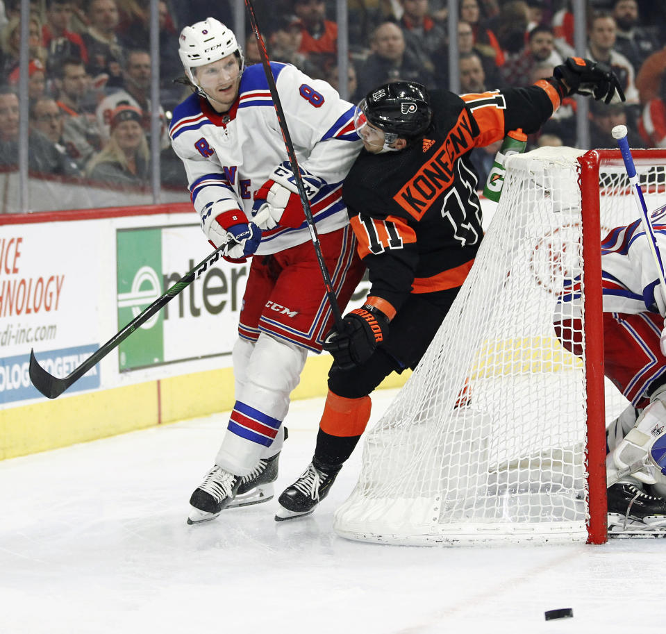 New York Rangers' Jacob Trouba shoves Philadelphia Flyers' Travis Konecny into the net as the two chase the puck during the second period of an NHL hockey game, Monday, Dec. 23, 2019, in Philadelphia. (AP Photo/Tom Mihalek)