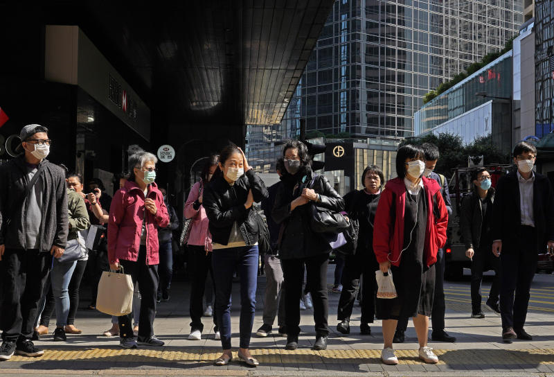 People wearing face mask walk at a downtown street in Hong Kong Friday, Feb. 21, 2020. COVID-19 viral illness has sickened tens of thousands of people in China since December. (AP Photo/Vincent Yu)