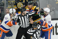 Referees keep Boston Bruins left wing Nick Ritchie (21) from fighting with New York Islanders left wing Matt Martin (17) and right wing Cal Clutterbuck (15) in the first period of Game 1 during an NHL hockey second-round playoff series, Saturday, May 29, 2021, in Boston. (AP Photo/Elise Amendola)