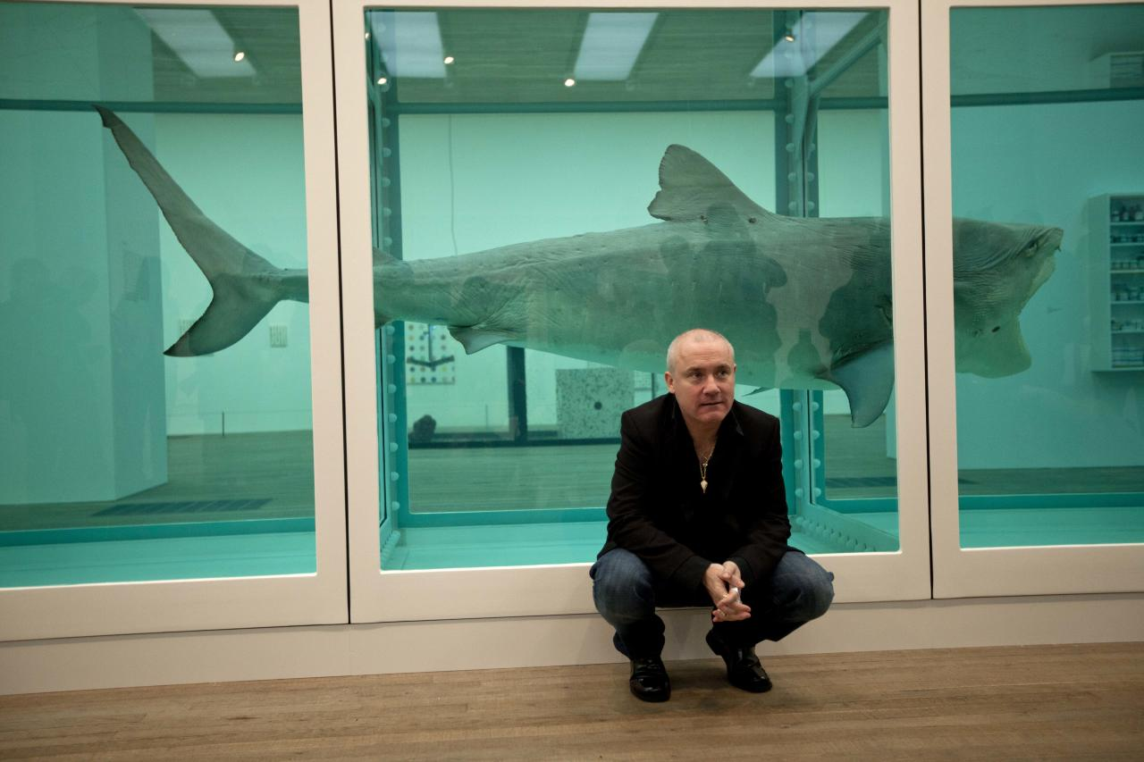"British artist Damien Hirst beside the 1991 piece ""The Physical Impossibility of Death in the Mind of Someone Living"", a tiger shark preserved in formaldehyde in a vitrine, during a media preview of the first substantial survey show of his work in the UK at the Tate Modern gallery in London, Monday, April 2, 2012. The exhibition, timed for the culmination of the Cultural Olympiad and due to open to the public on Wednesday, showcases over 70 of Hirst's works since he first came to public attention in 1988. (AP Photo/Matt Dunham)"